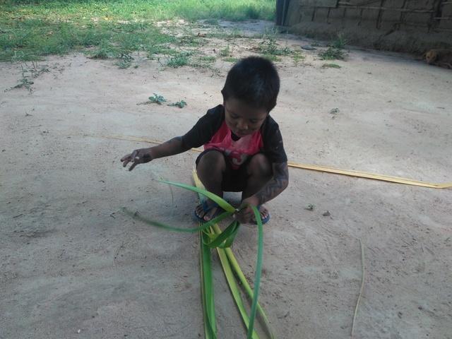 Criança Kujubim aprendendo a trançar a esteira (iwi) com palha. Foto: Gabriel Sanchez, 2018.